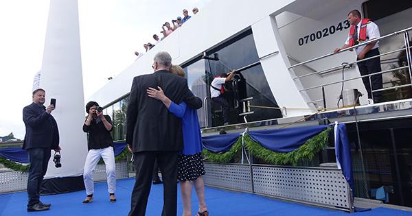 AmaWaterways co-owner Rudi Schreiner hugging Jackie as passengers look on from AmaViola.